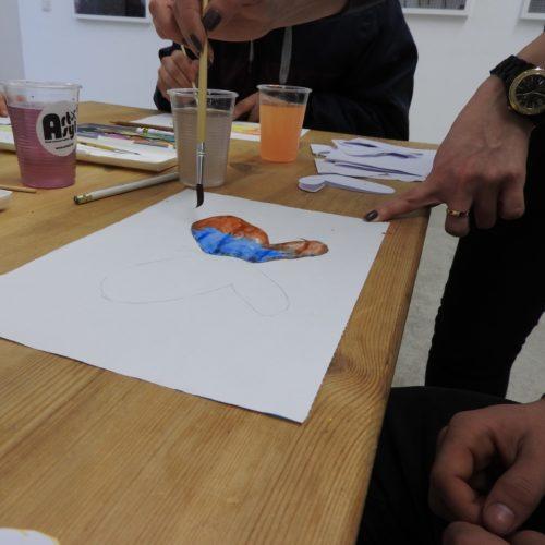 Ein halb mit Wasserfarbe ausgemalter bunter Schmetterling, eine Hand mit einem Pinsel. Auf dem Tisch ein Becher mit ArtAsyl-Logo und buntem Wasser